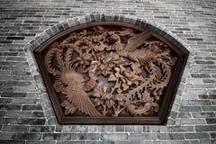 两只与花的飞行的中国天鹅周围墙壁雕塑  免版税库存照片