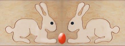 两只复活节兔子坐有害,与被形成的串的形状 免版税图库摄影