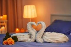 两只天鹅由毛巾制成在床在旅馆客房 免版税库存照片