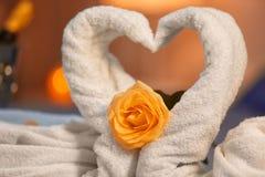 两只天鹅由毛巾和玫瑰色花制成在被弄脏的背景,特写镜头 免版税库存图片