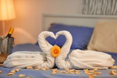 两只天鹅由毛巾和玫瑰花瓣制成在床在旅馆客房 库存图片