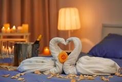 两只天鹅由毛巾和玫瑰花瓣制成在床在旅馆客房 免版税库存照片