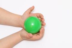 两只小手在他的手上的拿着球 图库摄影