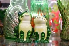 两只愉快的装饰青蛙注视向上围拢由绿色和桃红色玻璃 图库摄影