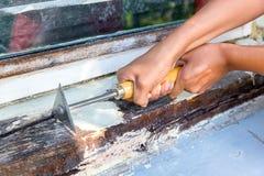 两只手与油漆刮板一起使用 免版税库存图片