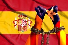 两只手卡塔龙尼亚的旗子桎梏了在西班牙的旗子的背景的一个金属链子 库存图片