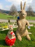 两只手工制造秸杆复活节兔子在庭院里 免版税库存照片