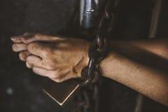 两只手得到了束缚与在酒吧囚犯的挂锁 库存照片