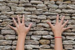 两只手接触了一个石墙 免版税库存照片