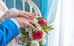 两只手新娘在一件白色礼服和一套蓝色衣服,说谎在英国兰开斯特家族族徽花花束  水平的框架 库存照片