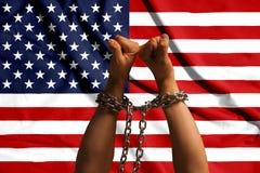 两只手桎梏了在美国旗子的背景的一个金属链子 免版税库存照片