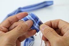 两只手缝合与针的镶边蓝色布料 库存图片