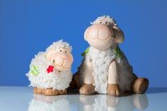 两只滑稽的绵羊小雕象在蓝色背景前面的 免版税库存照片