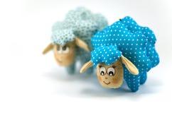 两只玩具羊羔,一集中蓝色有斑点的第二块绿松石玷污不在焦点于白色背景 免版税图库摄影