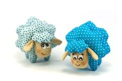 两只玩具羊羔,一集中蓝色有斑点的第二块绿松石玷污不在焦点于白色背景 免版税库存照片