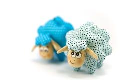 两只玩具羊羔,一集中绿松石被玷污的其次蓝色玷污不在焦点于白色背景 免版税库存图片