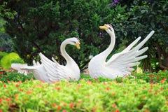 两只白色天鹅庭院雕塑在花的停放 免版税库存图片