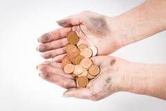 两只肮脏的手被隔绝在拿着硬币的白色背景 免版税图库摄影