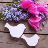 两只装饰鸟和淡紫色andtulips花在葡萄酒w 库存图片