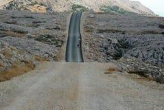 两只绵羊黑白在黑山路和岩石领域 免版税图库摄影