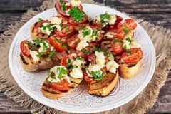 两叮咬烤开胃菜bruschettas用红葡萄蕃茄、无盐干酪和荷兰芹洒 免版税库存图片