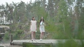 两可爱的女服站立在岩石上面和看自然的令人惊讶的看法夏天礼服 俏丽的女孩 影视素材