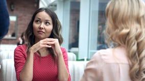 两可爱的妇女谈话与一位男性侍者 图库摄影