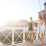 两可爱的妇女走和谈话在桥梁户外 免版税库存图片