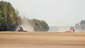 两台强有力的拖拉机犁,耕种在热的晴朗的天气的旱田在具球果森林背景许多 影视素材