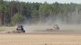 两台强有力的拖拉机犁,耕种在热的晴朗的天气的旱田在具球果森林背景  股票视频