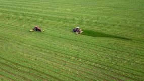两台拖拉机割在一张绿色领域鸟瞰图的草 免版税库存照片