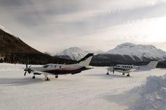 两台推进器类型私人喷气式飞机和飞机在积雪的机场在阿尔卑斯瑞士在冬天 免版税库存图片