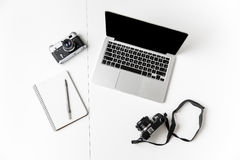两台照相机、笔记薄与笔和黑屏膝上型计算机 库存图片