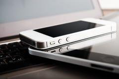 两台电话和片剂个人计算机在膝上型计算机 免版税图库摄影