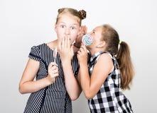 两吃明亮的棒棒糖的逗人喜爱的矮小的女朋友 滑稽的孩子 最好的朋友纵容和摆在 他们中的一个耳语 图库摄影