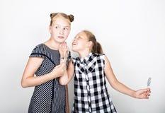 两吃明亮的棒棒糖的逗人喜爱的矮小的女朋友 滑稽的孩子 最好的朋友纵容和摆在 他们中的一个耳语 免版税库存照片