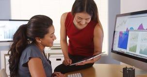 两名不同种族的女实业家谈话与片剂在书桌 免版税库存照片