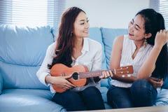 两名亚洲妇女获得演奏尤克里里琴和微笑在的乐趣ho 库存照片