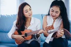 两名亚洲妇女获得演奏尤克里里琴和微笑在的乐趣ho 免版税图库摄影