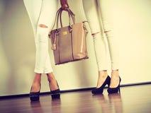两名亭亭玉立的妇女与皮包提包 免版税库存图片