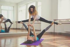 两名亭亭玉立的妇女做着平衡锻炼 图库摄影