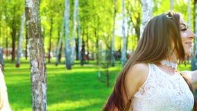 两名俏丽的妇女画象跳舞在被日光照射了桦树树丛里的时髦的服装的 影视素材