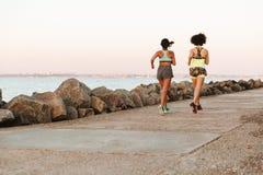 两名健身妇女跑的全长后面看法图象 图库摄影