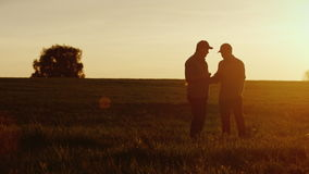 两名农夫工作者在领域沟通,使用片剂 在美好的日落 股票录像