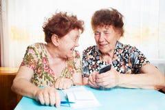 两名前辈妇女考虑收据 图库摄影
