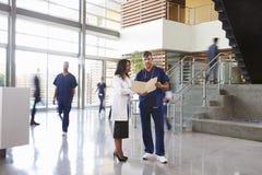 两名医疗保健工作者在一家繁忙的医院的大厅谈话 免版税库存照片