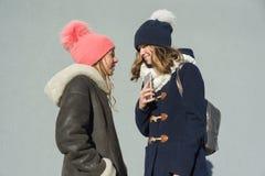 两名十几岁的女孩的学生一张室外冬天画象的特写镜头谈话外形的微笑和 免版税库存图片