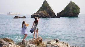 两名可爱的妇女停留和享用在大石头由海 影视素材