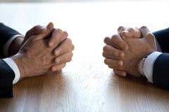 两名商人谈判员对手对面的被扣紧的手在桌上的 库存照片