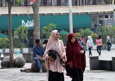 两名回教妇女印度尼西亚走在Fatahillah广场在老镇邻里在雅加达 免版税库存照片